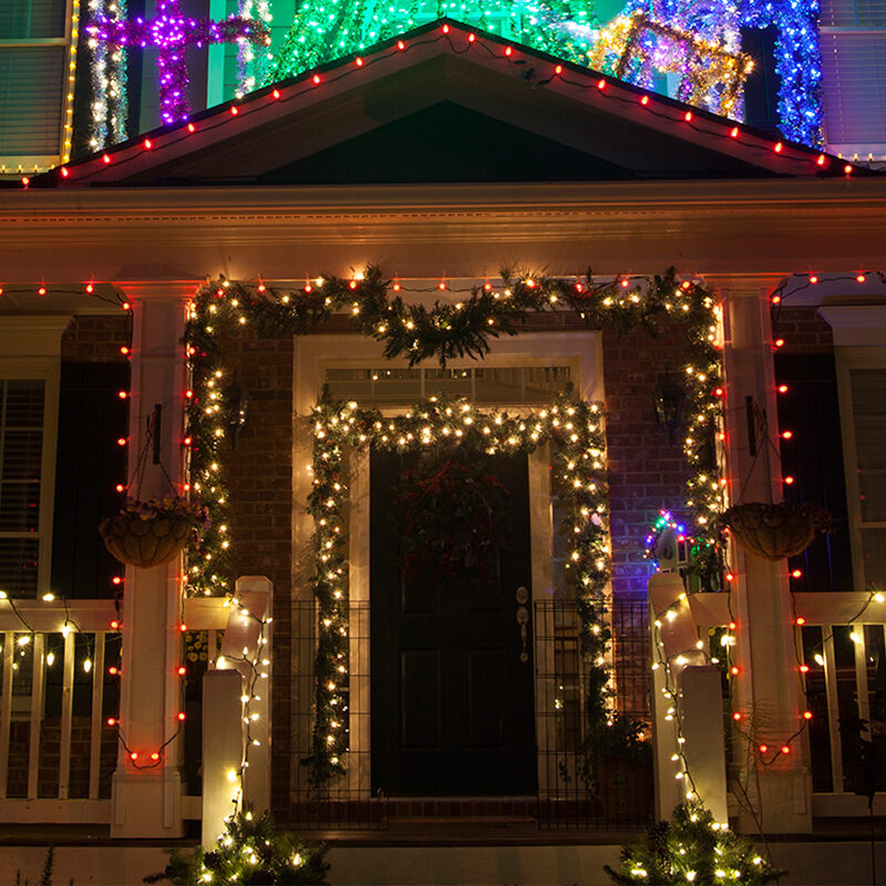 Porch decorated with Christmas garland and string lights.